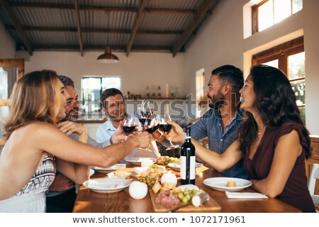 group of friends toasting glasses of wine during meal stock photo © wavebreak_media