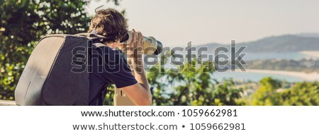 bunner man looks in coin operated binoculars at the sea stock photo © galitskaya