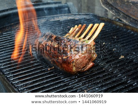 Flame rises from a grill around barbecued meat Stock photo © sarahdoow