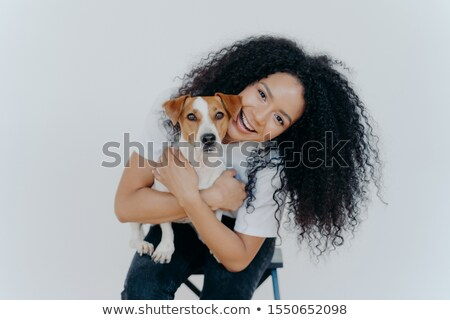 Happy curly woman tilts head, holds pedigree dog, has cheerful expression, smiles pleasantly, has cu Stock photo © vkstudio