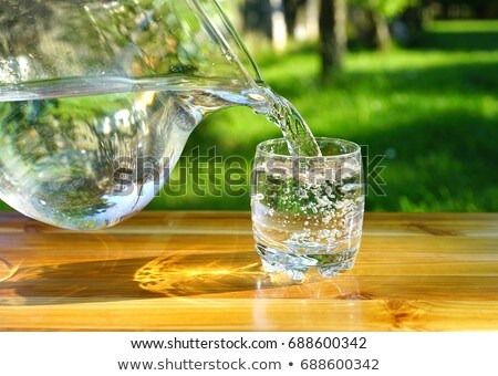 Pouring Water into a Glass against the Green Nature Background Stock photo © maxpro