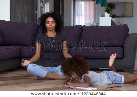 Woman doing yoga while sitting in lotus yoga pose stock photo © wavebreak_media