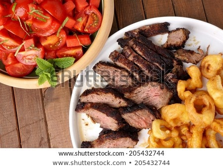 Flank steak with fries onion rings and salad Stock photo © Klinker