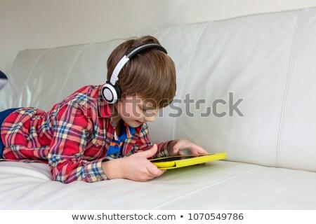 Cute weinig jongen smartphone hoofdtelefoon ligstoel Stockfoto © galitskaya