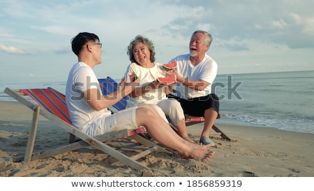 Happy family Father and son eating a watermelon on the beach. Children eat healthy food Stock photo © galitskaya