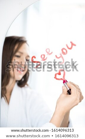 Hand of happy female writing see you and drawing heart with lipstick on mirror Stock photo © pressmaster