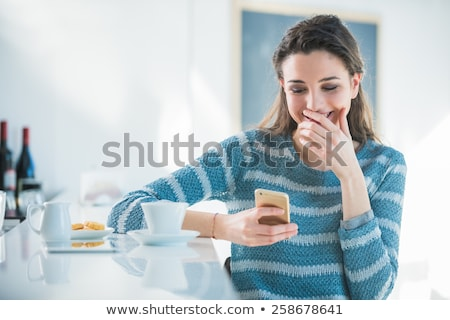 a woman laughing at a text message stock photo © is2
