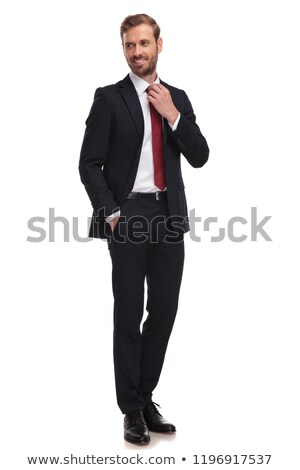 relaxed businessman fixes his red tie and looks to side Stock photo © feedough