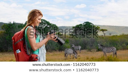 woman with backpack and camera over savannah Stock photo © dolgachov