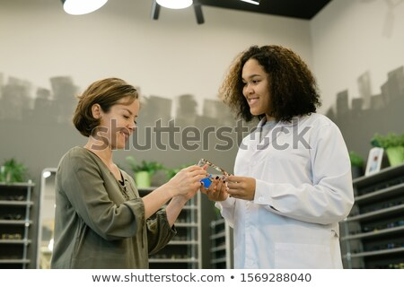 Pretty young consultant of optics shop showing new eyeglasses to one of clients Stock photo © pressmaster