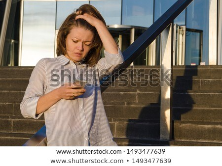 Unhappy woman clutching her mobile phone Stock photo © photography33