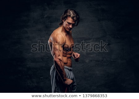 Attractive musculous guy lifting weight Stock photo © ra2studio