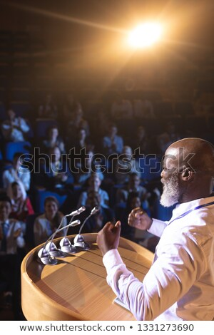 High angle view of old African-American businessman standing  and holding speaker while asking quest Stock photo © wavebreak_media