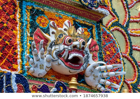 Bade cremation tower with traditional balinese sculptures of demons and flowers on central street in Stock photo © galitskaya