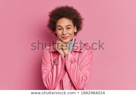 Lovely millennial female looks with satisfied expression at camera, has long hair, dressed in stylis Stock photo © vkstudio