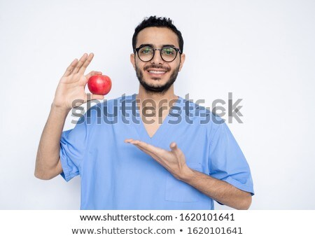 Young smiling clinician in blue uniform showing you ripe red apple Stock photo © pressmaster
