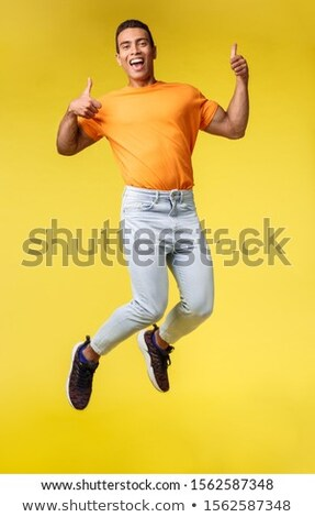 Full-length vertical shot cheerful masculine hipster guy in trendy orange t-shirt, white pants, jump Stock photo © benzoix