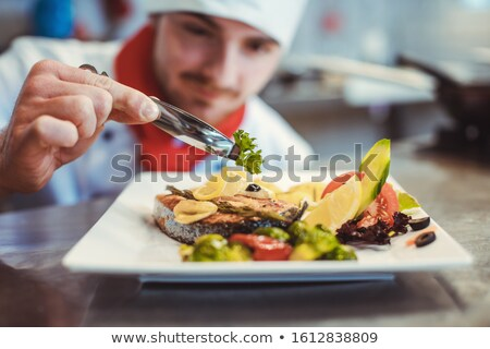 Proud chef garnishing an almost finished dish in the restaurant with leave Stock photo © Kzenon