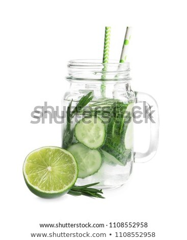 Fresh cold cucumber water with ice cubes and cucumber slices on white. Healthy and refreshing organi Stock photo © DenisMArt