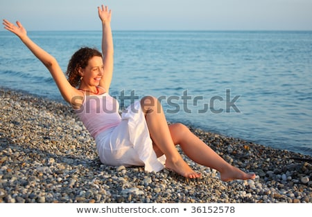 young woman sits ashore of sea with rised hands Stock photo © Paha_L