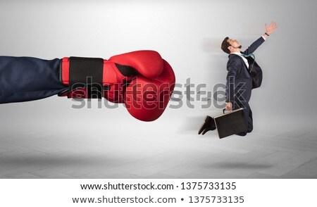 Giant hand gives a kick to a small businessman Stock photo © ra2studio