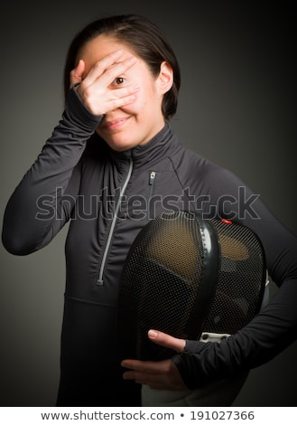 female fencer peeking through hands covering face stock photo © bmonteny