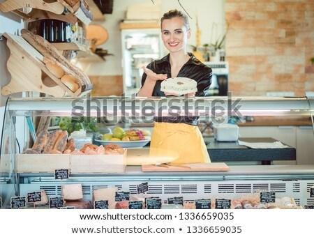 Salesgirl selling cheese in deli or supermarket Stock photo © Kzenon