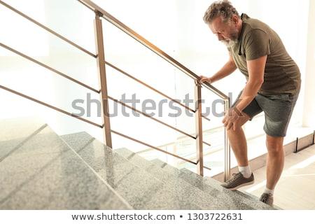 Senior man lijden knie pijn home Stockfoto © dolgachov
