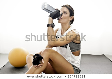 Tired young gym instructor drinking water Stock photo © stockyimages