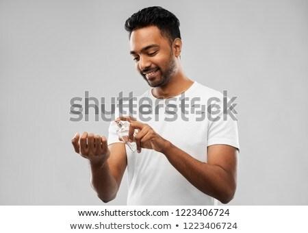 happy indian man with perfume over grey background stock photo © dolgachov