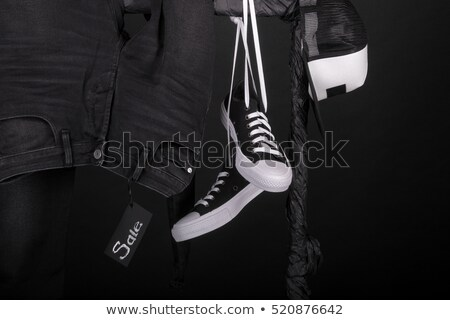 Sale sign. Black and white snaekers, cap and pant, jeans hanging on clothes rack on black background Stock photo © Illia