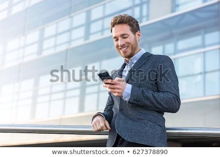 молодые деловой человек смартфон городского город расслабляющая Сток-фото © Maridav