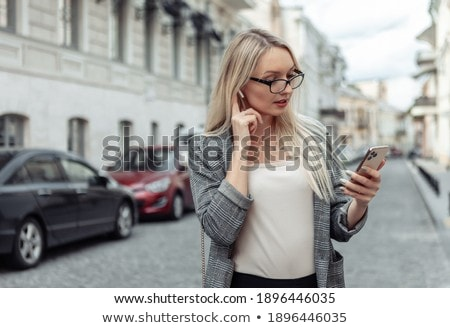 Portrait of an attractive woman in suit using headphones and posing while standing against a white b stock photo © wavebreak_media