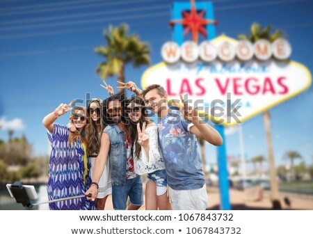 friends taking selfie by monopod at las vegas sign Stock photo © dolgachov