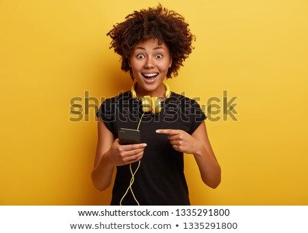 Joyous african american woman in casual clothing listening to mu Stock photo © deandrobot
