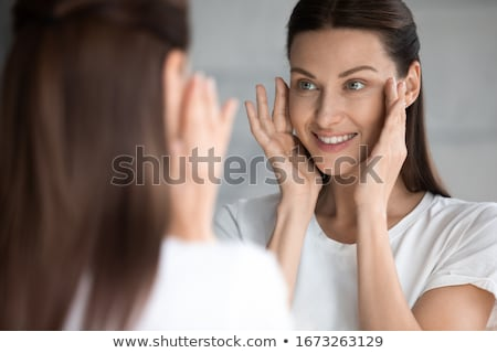 Beautiful young woman looking at the mirror at the bathroom Stock photo © deandrobot