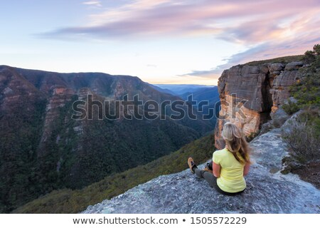woman with wind swept hair sitting on edge of cliffs stock photo © lovleah