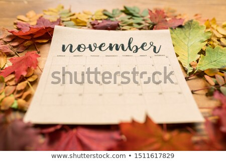 November calendar on paper sheet surrounded by autumn leaves of vivid colors Stock photo © pressmaster