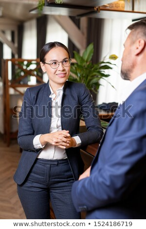 Elegant woman of Asian ethnicity discussing some working moments with colleague Stock photo © pressmaster