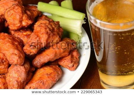 Hot chicken wings and draft beer Stock photo © karandaev