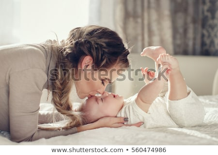 Stock photo: Young mother feeding her newborn child.