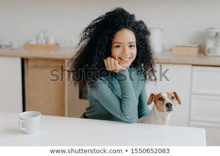 Photo of pleasant looking woman dressed in casual wear, has curly bushy hair, poses against kitchen  Stock photo © vkstudio