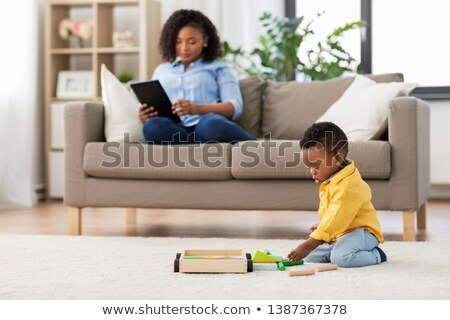 baby playing toy blocks and mother using tablet pc Stock photo © dolgachov