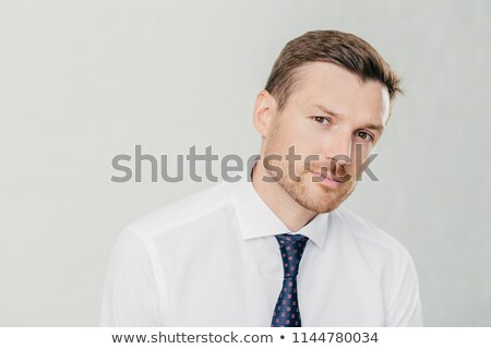 Confident male looks seriously at camera, has dark eyes and stubble, dressed in elegant white shirt  Stock photo © vkstudio