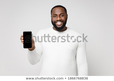 Image of young man wearing basic clothes smiling and holding cellphone Stock photo © deandrobot