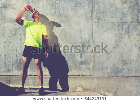 young sweaty man having a break in workout stock photo © ammentorp