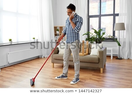 man with broom cleaning and calling on smartphone Stock photo © dolgachov