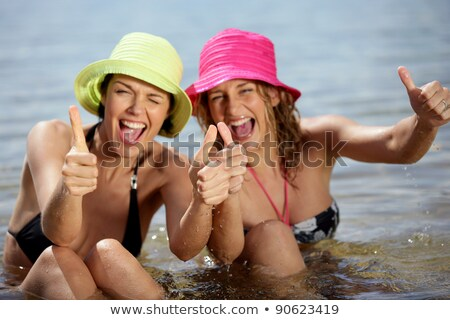 Two female friends at the beach giving thumbs-up Stock photo © photography33