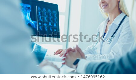 Female doctor working in hospital with patient and x-rays Stock photo © diego_cervo