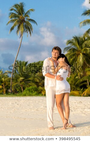 Man and woman standing in an embrace and watch the sunset Stock photo © Kotenko